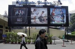 People walking past movie billboards outside a cinema in Jakarta