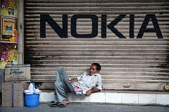 Man reading a newspaper beneath Nokia logo in Kolkata, India