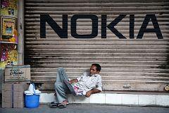 Man reading a newspaper beneath Nokia logo in Kolkata, India