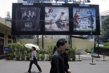 People walk past movie banners outside a movie theater in Jakarta, Indonesia (File Photo - February 21, 2011)